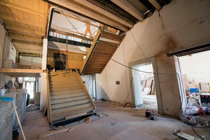 De gerestaureerde trap van het oude stadhuis in Harderwijk hangt in de kettingen en wordt terug op zijn plaats gehesen.