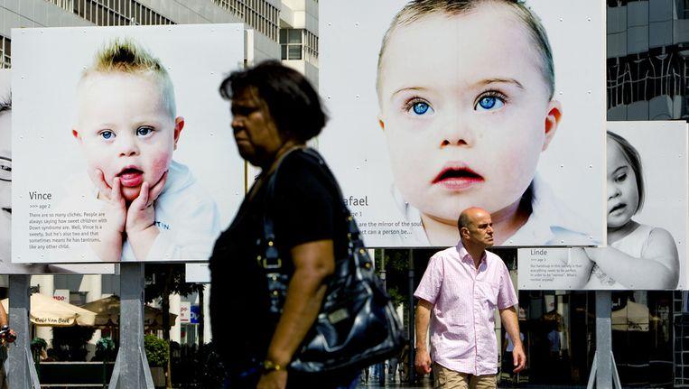 Voorbijgangers lopen woensdag langs grote portretfoto's van kinderen met het Downsyndroom op het Spuiplein in Den Haag Beeld anp
