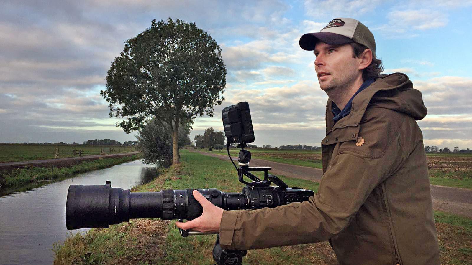 De filmmaker in actie tijdens zijn werkzaamheden in de natuur.