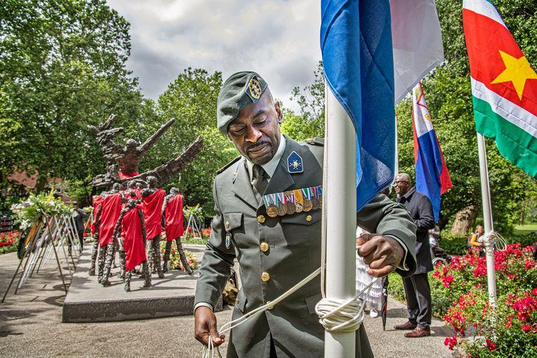 Een militair haalt de Nederlandse vlag neer bij het slavernijmonument in het Oosterpark, na het officiële programma rond Ketikoti. Beeld Guus Dubbelman / de Volkskrant