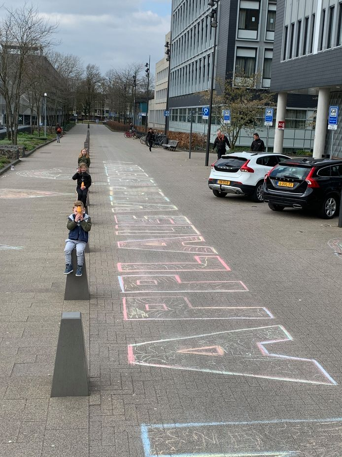Fenna, Milo en Brechje stoepkrijten een grote tekening bij het Catharina Ziekenhuis in Eindhoven om het zorgpersoneel te steunen.