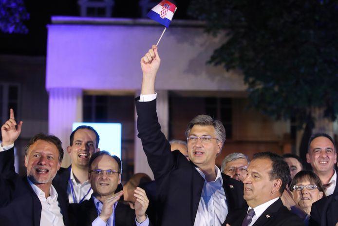 Zittend premier Andrej Plenkovic (midden) van Kroatië viert de winst bij de parlementsverkiezingen.