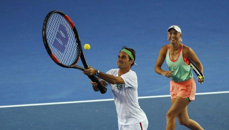 Roger Federer (34), met een reuzeracket, en Caroline Wozniacki (25) tijdens de Kids Tennis Days, zaterdag in Melbourne. Beeld Issei Kato/Reuters