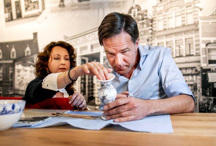 Premier Mark Rutte beschildert een Delfts blauw vaasje in de fabriek van Heinen Delfts Blauw in Putten.