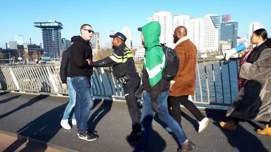 Op de brug probeert een jonge man de stoet in zijn eentje -met een metgezel aan zijn zijde- te stoppen. De politie houdt hem tegen.