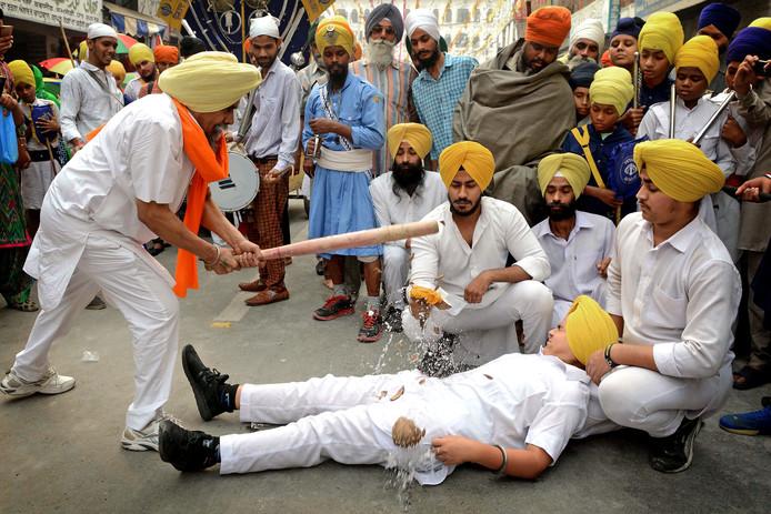 Au! In het Indiase Amritsar voert een Sikh een 'Gatka' uit. Hierbij wordt met een honkbalknuppel een kokosnoot op iemands kruis in tweeën geslagen. Foto: Narinder Nanu