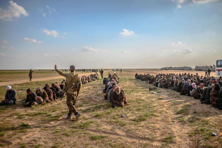 Mannen die ervan verdacht worden IS-strijder te zijn, wachten op hun ondervraging door Syrische strijdkrachten.