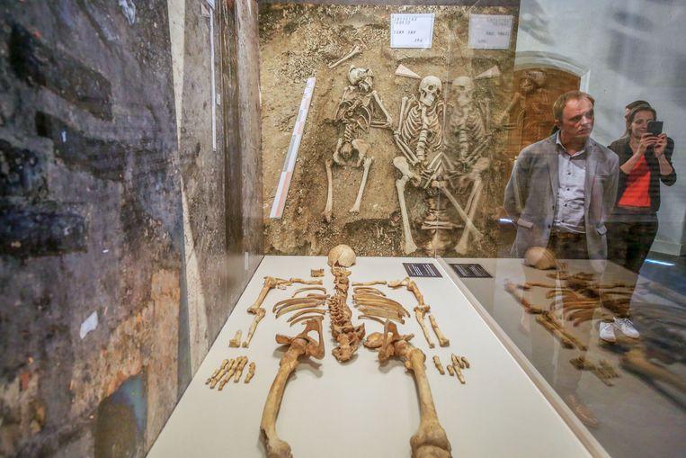 Een van meer dan 1.200 skeletten die tijdens de opgravingen werden bovengehaald. Schepen Soenen is heel geïnteresseerd. De man is amateur-archeoloog en hielp ook mee tijdens de opgravingen.