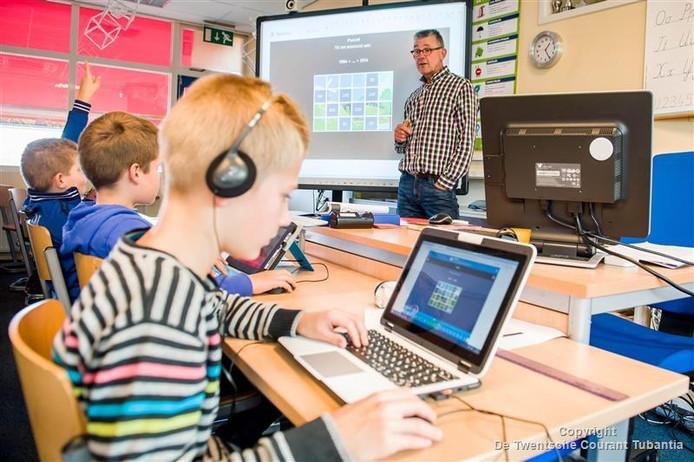 Gerard Welberg met zijn leerlingen bezig met Snappet, een digitale lesmethode.