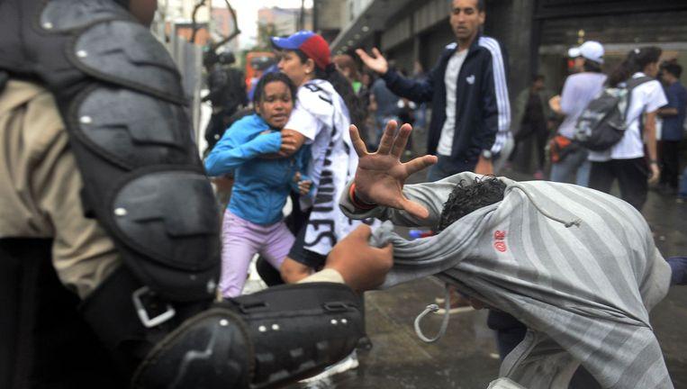 Een tegenstander van president Maduro wordt handhandig gearresteerd tijdens het protest in Caracas gisteren.