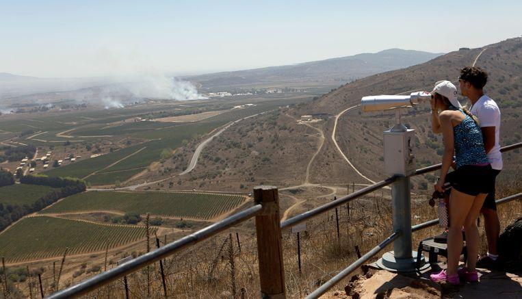 Israëli kijken naar de rook na de Syrische gevechten op de Golan hoogvlakte. Beeld EPA