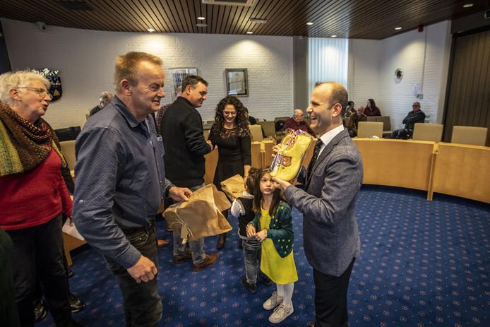 Na de naturalisatieceremonie, ontvangt nieuwe Nederlander Henry Shado klompen van zijn collega's. Op de achtergrond zijn vrouw Fimi Balta.