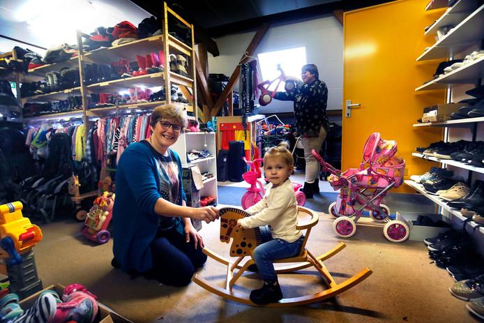 Gerrie met haar kleindochter Tessa in de zaak. Gieni op de achtergrond.