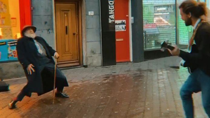 Oude man gaat los op muziek van straatmuzikant  in centrum Den Haag.