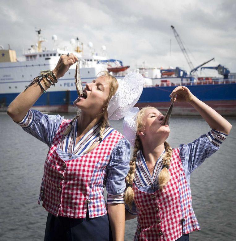 Twee dames in klederdracht proeven een haring uit het eerste vaatje Hollandse Nieuwe over de kade van Scheveningen haven. Beeld ANP