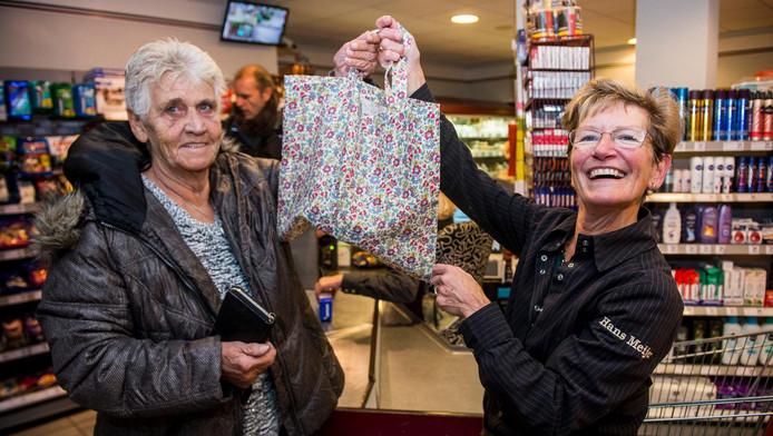 Nelly¿Meijer (rechts) verblijdt haar klant Riet Bos met een gratis stoffen tasje, gemaakt door de 76-jarige Rieneke van der Wansem.