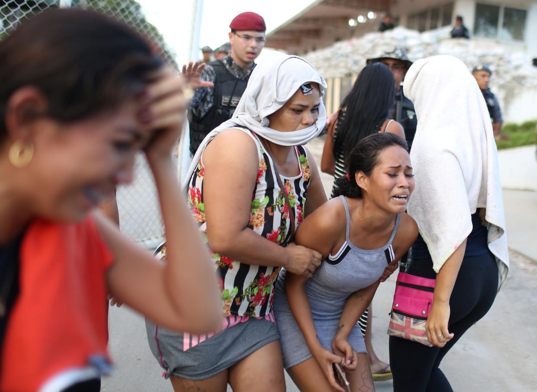 Familieleden van gedetineerden barsten in tranen uit voor een gevangeniscomplex in de Braziliaanse staat Amazonas, nadat zij het nieuws over de geweldsuitbarstingen te horen hebben gekregen. Beeld Reuters/Bruno Kelly
