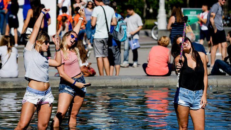 Toeristen zoeken verkoeling in het water op het Museumplein. Beeld anp