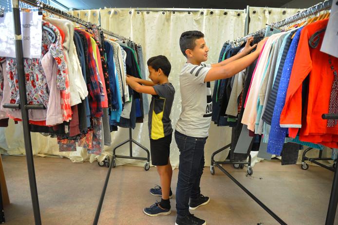 Yazan en Mousa (rechts) uit Hansweert zoeken bij de kledingbank in Middelburg een nieuwe winteroutfit uit.
