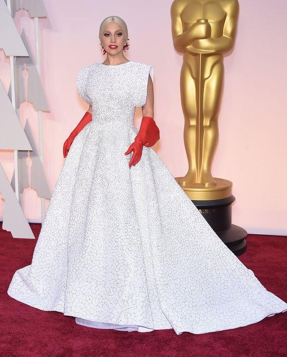 Lady Gaga kwam naar de Oscars in een wit kleed van Azzedina Alaïa en met opvallende rode handschoenen.