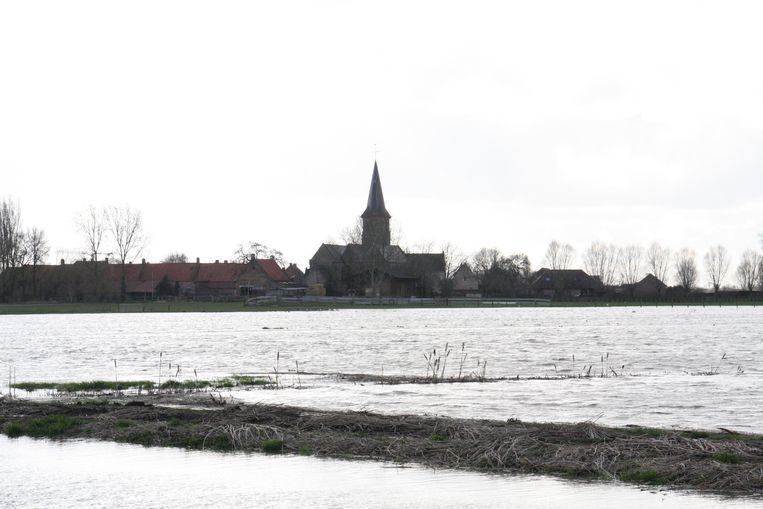 Ondergelopen weilanden met op de achtergrond de kerk van Noordschote