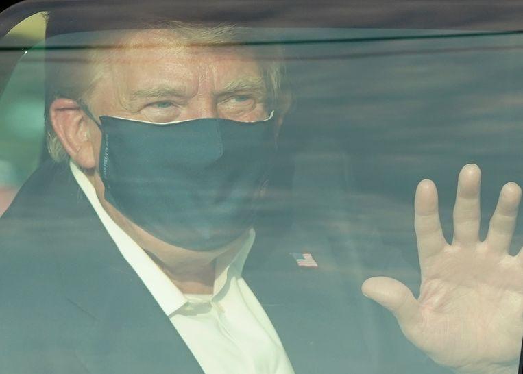 De Amerikaanse president Donald Trump maakte zondag een ritje rond het ziekenhuis waar hij op dat moment was opgenomen vanwege zijn coronabesmetting om naar aanhangers te zwaaien. Beeld AFP