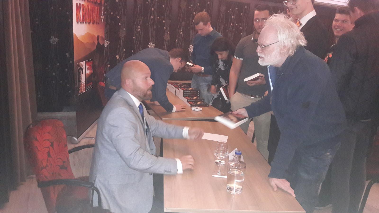 Marco Kroon signeert na zijn lezing bij de JOVD in Den Bosch zijn boek.