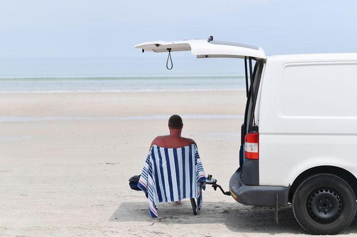 Een man zit in de schaduw van zijn busje op Aldinga Beach, ten zuiden van Adelaide.