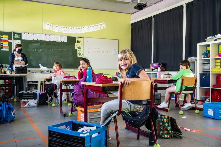 Blij gezichten in de klas omdat de school weer open is, ook al is dat in kleine groepjes.