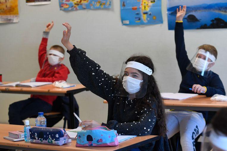 Schoolkinderen dragen mondkapjes in de les in een lokaal op het Claude Debussy college in Angers, Frankrijk. Beeld AFP