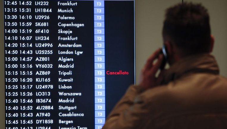 Een man kijkt op het vliegveld in Rome naar een bord waarop een afgelaste vlucht naar Tripoli staat. Beeld reuters