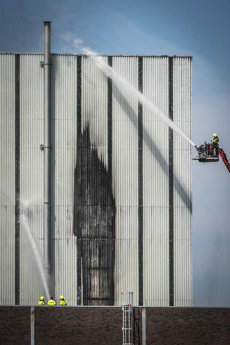 De brandweer blust een grote brand bij de voormalige kerncentrale Dodewaard. Er is geen risico op het vrijkomen van radioactieve straling door de brand. Wel wordt omwonenden geadviseerd ramen en deuren te sluiten en de ventilatie uit te schakelen als ze last van de rook hebben. Beeld Roland Heitink / ANP