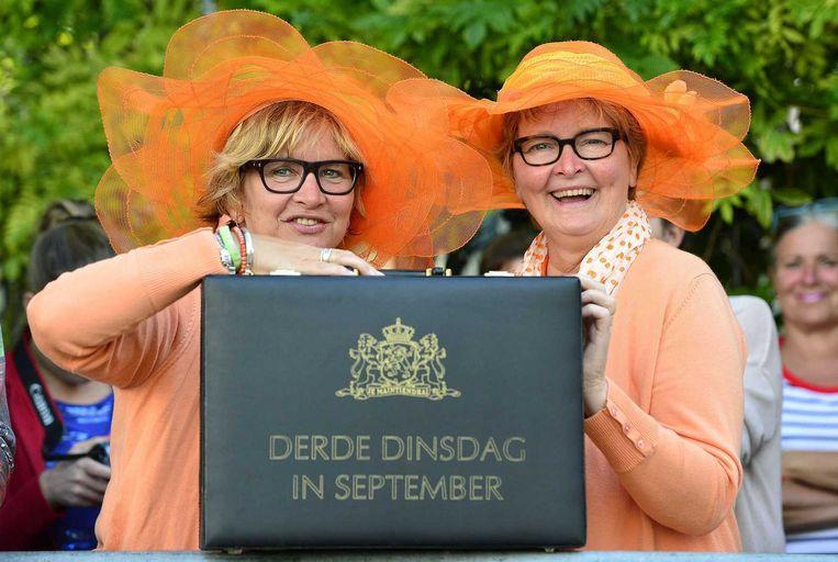 Twee vrouwen met oranje kleding tonen een replica van het koffertje van de Miljoenennota op Prinsjesdag 2014. Beeld anp