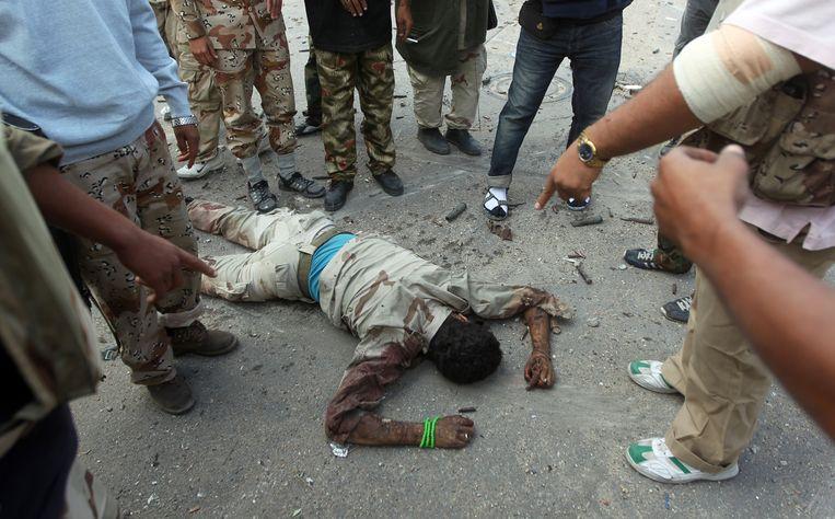 Rebellen verzamelen zich om het lichaam van een vermoorde Kaddafi-loyalist. Beeld AFP