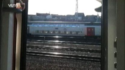 Trein rijdt met open deur tussen station Haaltert en Denderleeuw