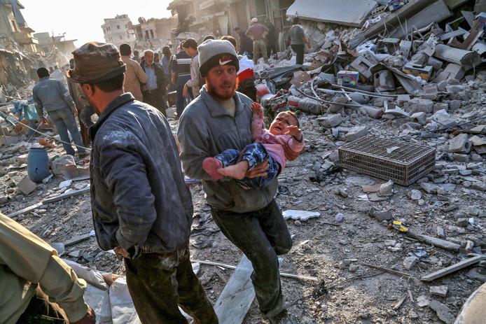 Een Syrische man haalt een baby uit de puinhopen na een bombardement van het Syrische leger in de door rebellen gecontroleerde stad Atareb. Foto Zein Al Rifai