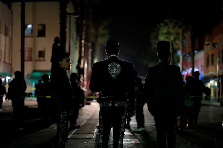 Drie van de vele mariachi's op het plein kijken toe op de plaats delict.