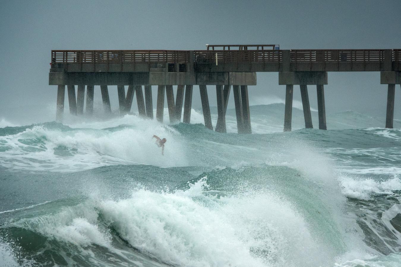 Een surfer langs de kust van Florida tijdens Isaias.