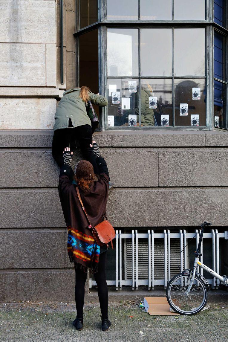 Een vrouw probeert door het raam het Bungehuis binnen te gaan. Beeld ANP