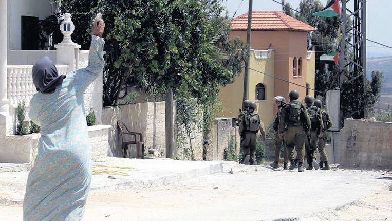 Een Palestijnse vrouw gooit een steen naar Israëlische soldaten in Kfar Kaddoem, nabij Nabloes, op de Westoever. Beeld afp
