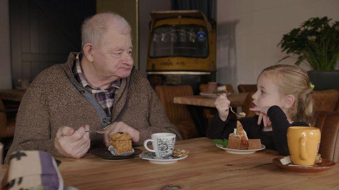 Theet Berendsen geniet samen met een meisje van een gebakje.