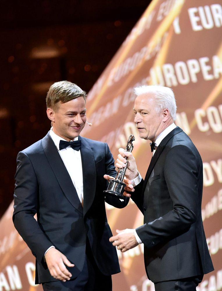 De Duitse acteur Thomas Wlaschihy overhandigt een award aan de Zweed Hannes Holm. Beeld epa