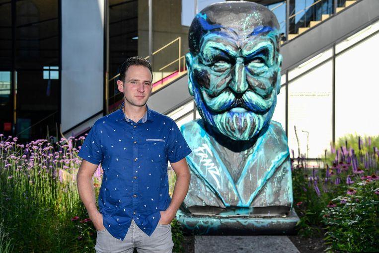 Bram Buytaert bij het standbeeld van Franz Courtens in de prairietuin van de bibliotheek.