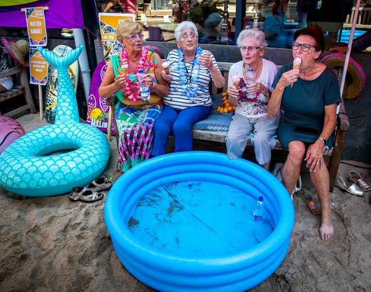 Ouderen van een zorgcentrum genieten van het zomerse weer. Om de bewoners vanwege de aanhoudende hitte wat verkoeling te geven is er een strandje aangelegd. Beeld Hollandse Hoogte /  ANP