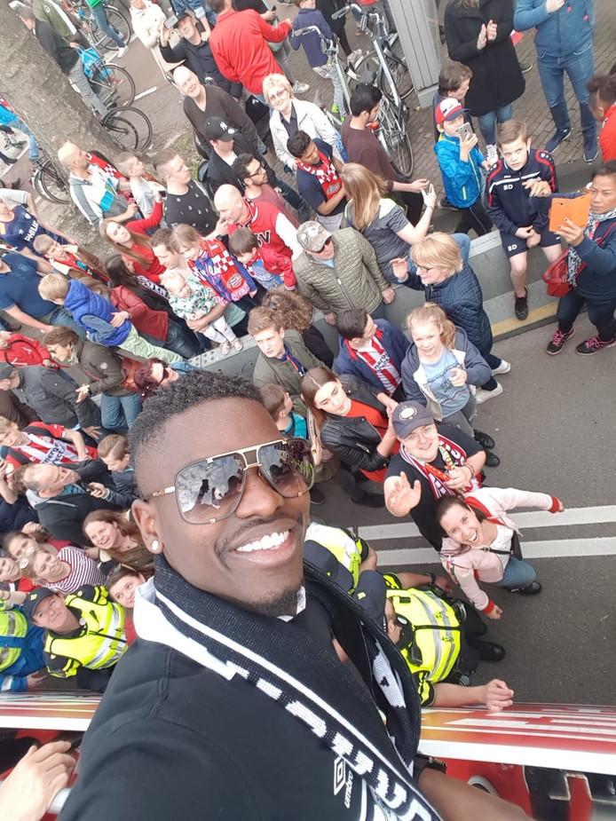 PSV'er Isimat maakt voor Germaine Hilgers een selfie vanaf de platte kar met haar op de achtergrond.