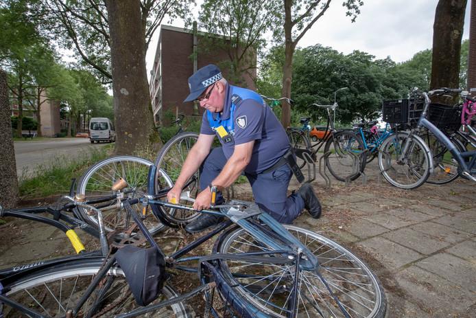 """Dick Verbeek van gemeente Wageningen plakt stickers op """"fietswrakken"""","""