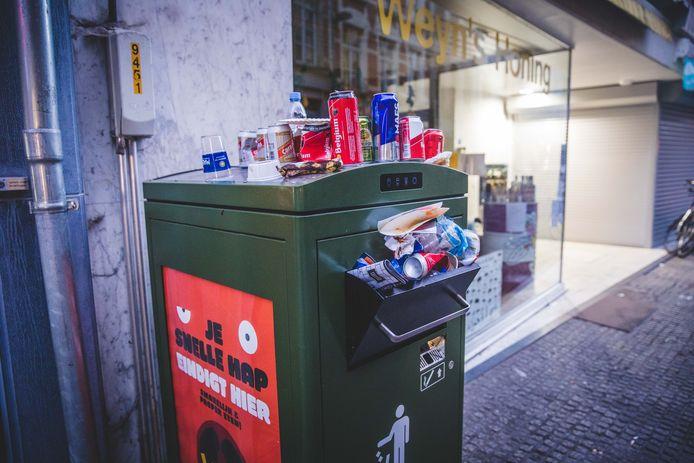Zwerfvuil bij een vuilnisbak.