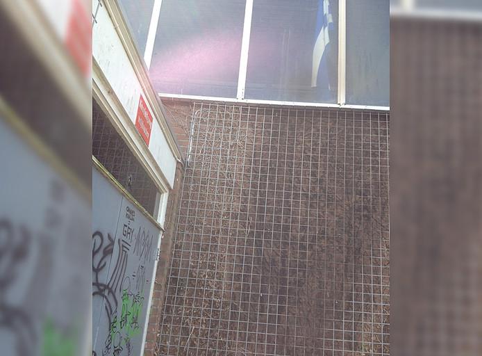 De zwartgeblakerde muur van de gymzaal aan de Nassaulaan.