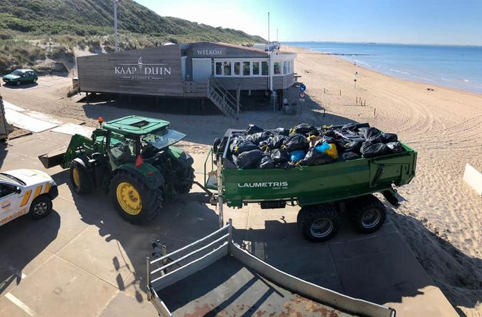 Een volle kar met afval verlaat het strand