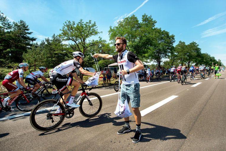 Anko Boelens, teamarts van Team Sunweb, deelt bij de bevoorradingingszone etenszakjes uit tijdens de Tour de France 2017. Beeld Klaas Jan van der Weij